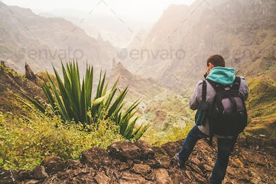 Santo Antao Island, Cape Verde. Hiking outdoor activity. Male traveler with backpack photographing