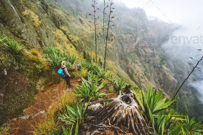 Santo Antao island at Cabo Verde. Female traveler staying on the cove volcano edge above the foggy