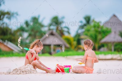 Two kids making sand castle and having fun at tropical beach