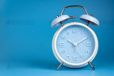 Old fashioned alarm clock on blue background