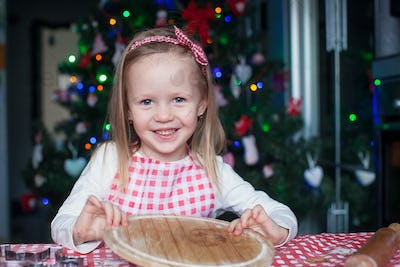 Adorable little girl baking gingerbread Christmas cookies at home
