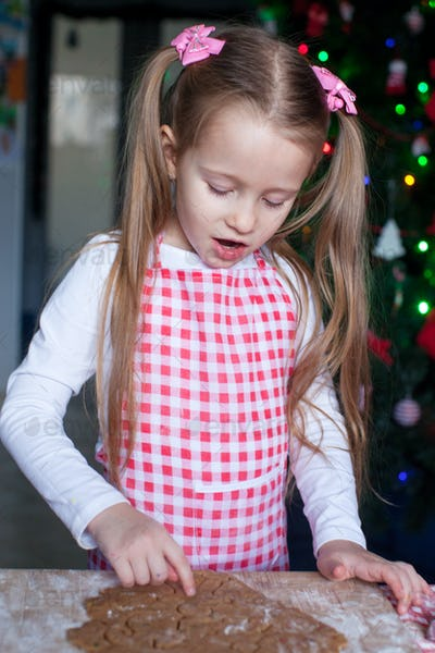Little girl baking gingerbread cookies for Christmas at home
