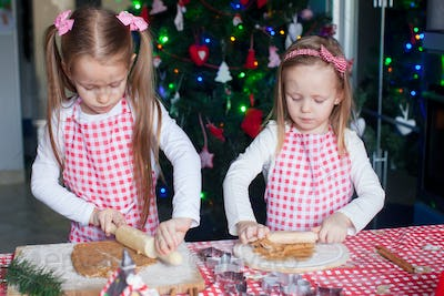 Two little adorable girls make gingerbread cookies for Christmas