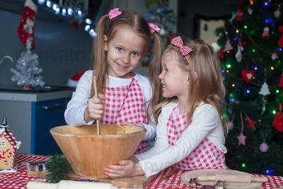 Little cute sisters bake gingerbread cookies for Christmas