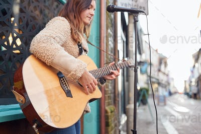 Female Musician Busking Playing Acoustic Guitar Outdoors In Street