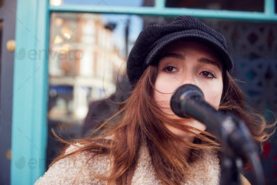 Female Musician Busking Singing Outdoors In Street