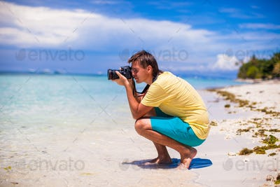 Young man taking pictures on a tropical beach