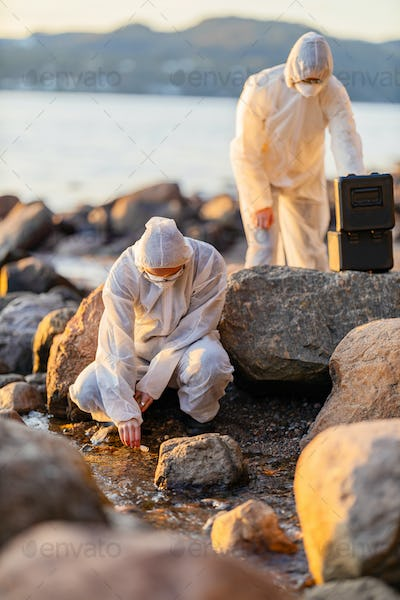 Scientist collecting water sample at the seashore