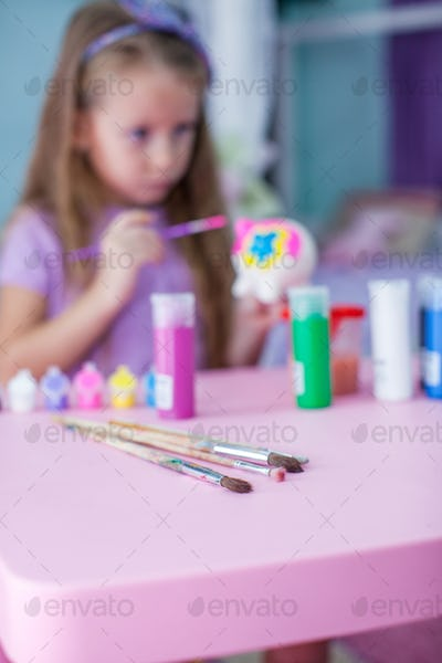 Little beautiful girl draws paints on the table