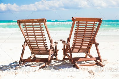 Beach wooden chairs for vacations and relax on tropical white sand plage