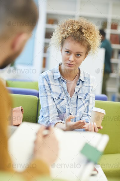 Teenage Girl Studying with Friend in Library