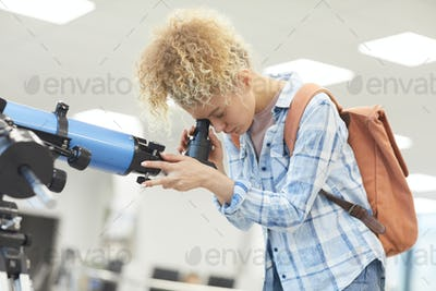 Young Woman Looking in Telescope during Astronomy Lesson