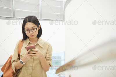 Asian Young Woman Using Smartphone in College