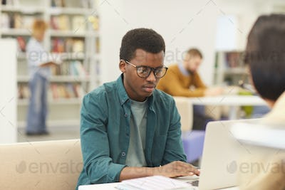 African Student Using Laptop in Library