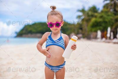 Little adorable girl in swimsuit rubs sunscreen herself