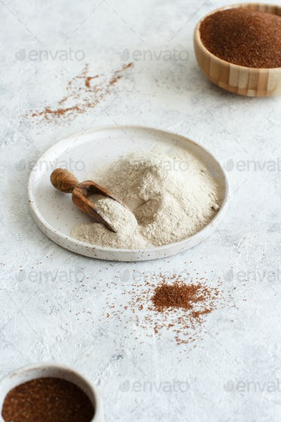 Teff flour on a plate with a spoon and teff grain