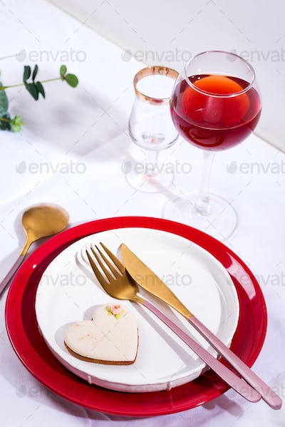 Tableware and decorations for serving a festive table. Plates, red wine glass and cutlery with green