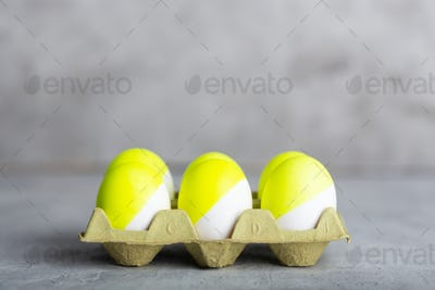 Six yellow painted eggs in tray on a gray concrete background