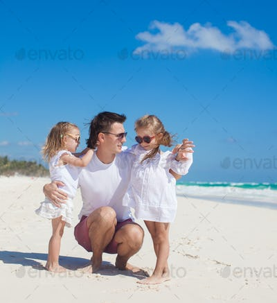 Happy father and his adorable little daughters on sunny day