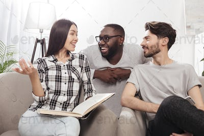 Group of young friends sitting on sofa at home and happily discussing something together