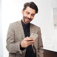 Young smiling businessman happily looking in cellphone in office