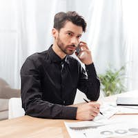 Man sitting at the table in office and talking on cellphone while thoughtfully looking aside