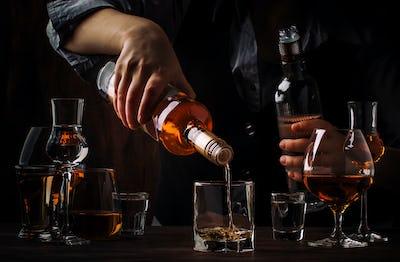 The bartender pours the dark golden rum
