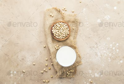 Soy milk and soy bean on beige background.