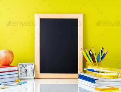 Chalkboard, apple and school supplies on white table by the yellow wall