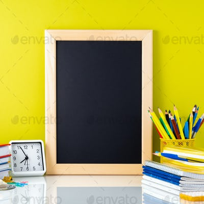 Chalkboard, textbooks, clock and school supplies on table