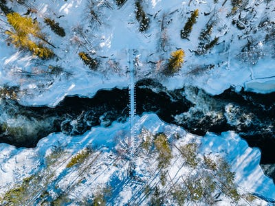 Aerial view of fast river with suspension foot bridge. Snow winter forest in Finland