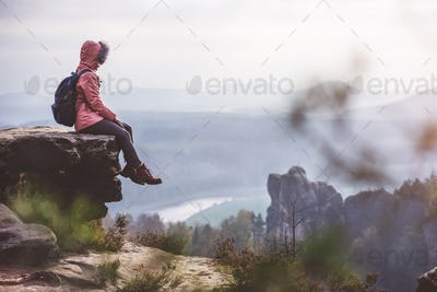 Young woman in outdoor clothing with backpack sitting on cliff's edge enjoying view of mountain