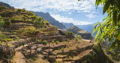 Hiker with camera among agriculture terraces nestled into the slopes of gorgeous mountains