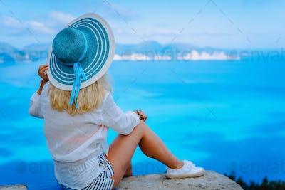 Attractive female tourist with turquoise sun hat enjoying amazing azure seascape, Greece. Cloudscape