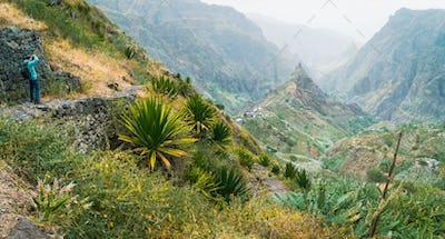 Photographer takes a picture of amazing lush Xo-Xo valley. Rugged Lombo de Pico in the middle. Santo