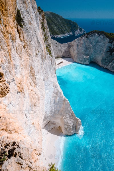 Limestone chalk colored like huge cliff rocks surrounding Navagio beach with Shipwreck and azure