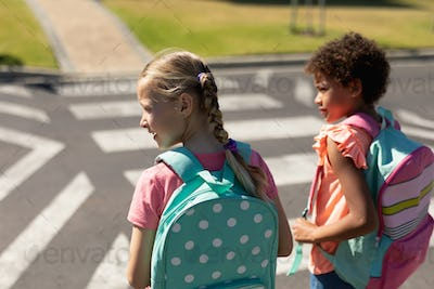 Two schoolgirls looking for traffic while waiting to cross the road