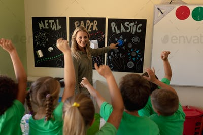 Female school teacher pointing to a recycling poster with a group of schoolchildren raising their ha