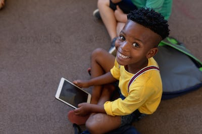 Schoolboy sitting cross legged on the floor using a tablet computer in an elementary school classroo