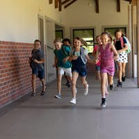 Group of schoolchildren running in an outdoor corridor at elementary school