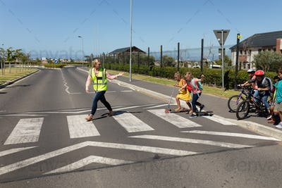 Woman wearing a high visibility vest on a pedestrian crossing