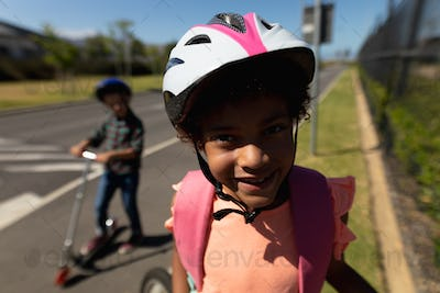 Schoolgirl wearing a cycling helmet and smiling to camera