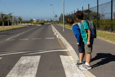 Two schoolboys looking for traffic while waiting to cross the road