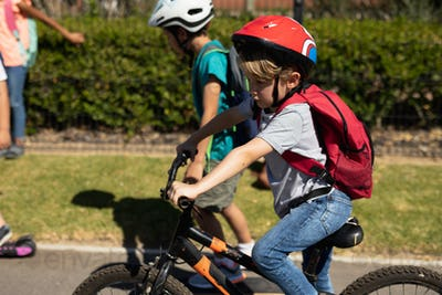 Schoolboy wearing a cycling helmet and riding a bicycle