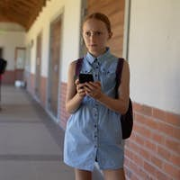 schoolgirl standing in the schoolyard at elementary school using a smartphone