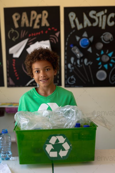 Schoolboy wearing a green t shirt with a white recycling logo on it