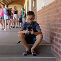 Schoolboy sitting on a step in the schoolyard at elementary school
