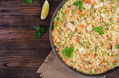 Bulgur with chicken, green peas and carrot  on wooden background. Top view