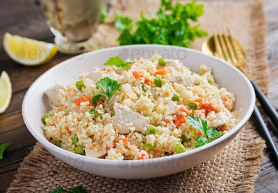 Bulgur with chicken, green peas and carrot  on wooden background.