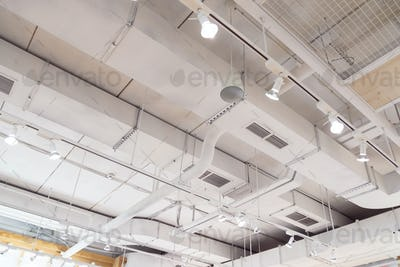 Ventilation ducts system painted in white composition of fire protection under the ceiling